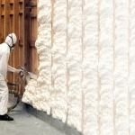 A man spraying on insulation to increase r-value